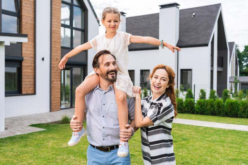 Nice cute girl sitting on her fathers shoulders royalty free stock photography