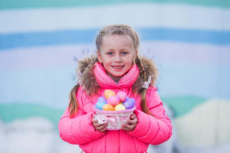 Nice cute little girl with two pigtails goes on a visit to the celebration of Easter with a basket of colorful eggs stock image