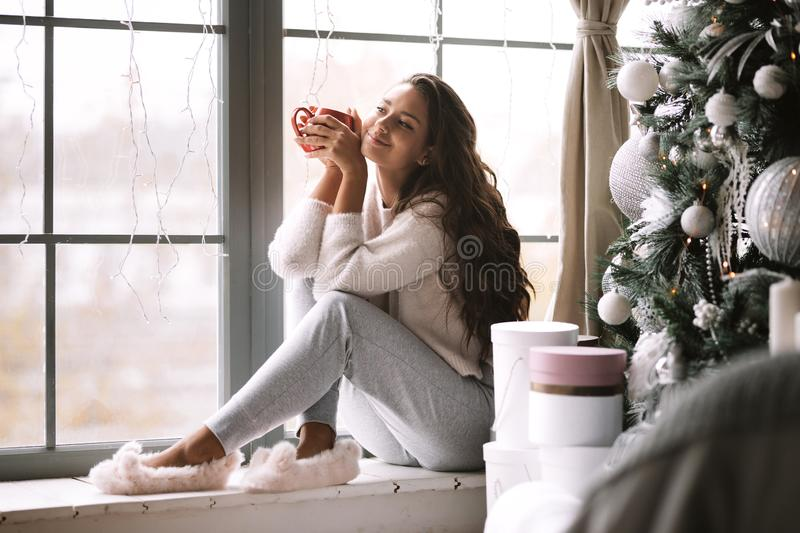 Nice dark-haired girl dressed in pants, sweater and warm slippers holds a red cup sitting on the windowsill of a. Panoramic window in the room next to the New stock photo
