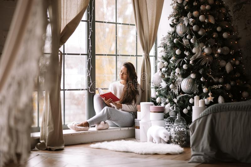 Nice dark-haired girl dressed in pants, sweater and warm slippers reads a book sitting on the windowsill of a panoramic. Window in the room next to the New Year royalty free stock photography