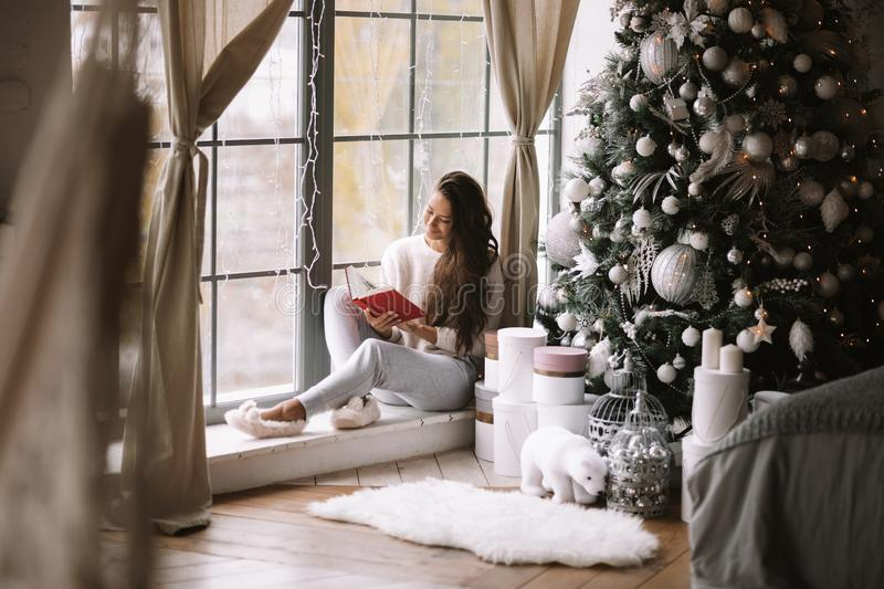 Nice dark-haired girl dressed in pants, sweater and warm slippers reads a book sitting on the windowsill of a panoramic. Window in the room next to the New Year royalty free stock photo