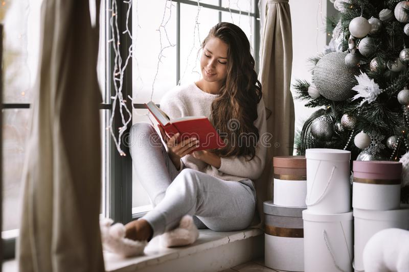 Nice dark-haired girl dressed in pants, sweater and warm slippers reads a book sitting on the windowsill of a panoramic. Window in the room next to the New Year royalty free stock image