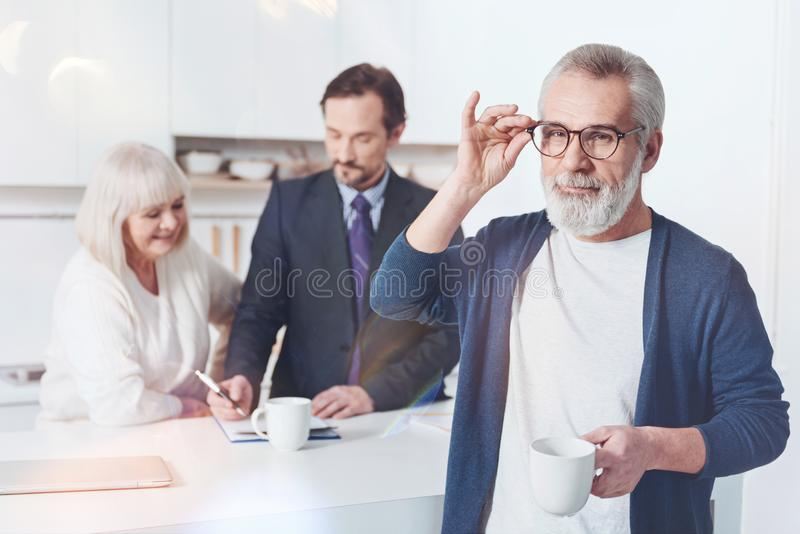 Positive elderly man meeting with insurance agent at home royalty free stock images