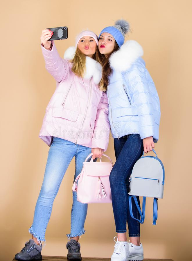 Nice day. xmas vacation. happy winter holidays. Students friendship. girls in beanie with bag. seasonal shopping. winter. Clothing fashion. down jacket. selfie royalty free stock photo