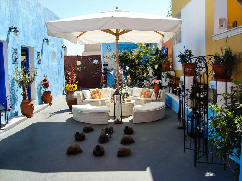 Nice decorated garden in Oia Santorini. Nice garden decorated with Artificial animals and flowers in Oia Santorini in a sunny day with sofas and sun umbrella royalty free stock image