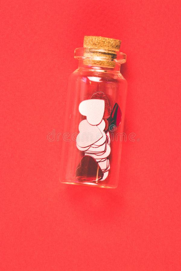 Nice decorative bottle with red shine confetti in the form of hearts on a red background. Valentines day concept stock images
