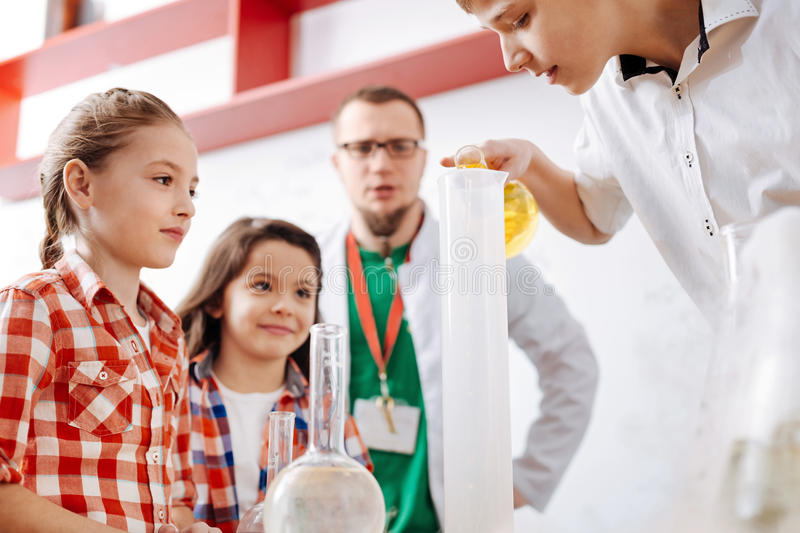 Nice delighted children carrying out a chemical experiment stock images