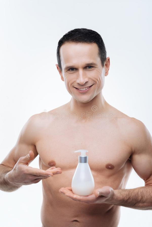 Nice delighted man presenting body lotion royalty free stock photos
