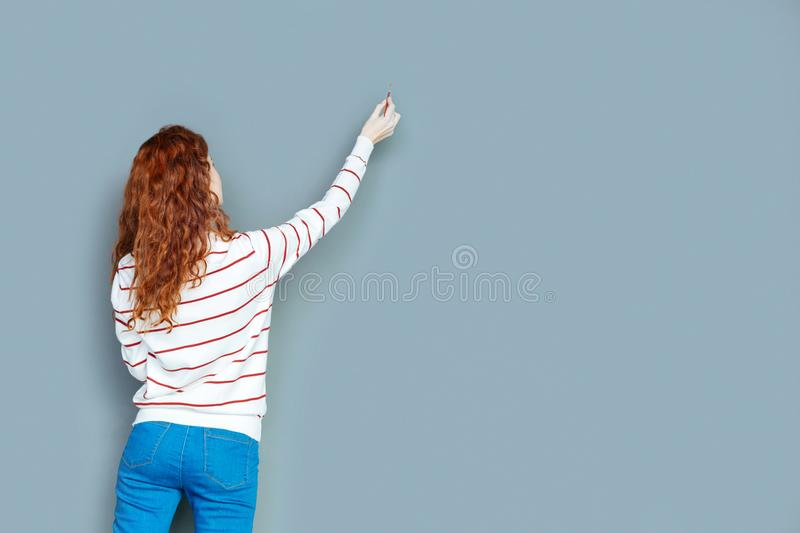 Nice delighted woman painting on the wall. Creative hobby. Nice delighted joyful woman holding a brush and looking at the wall while painting on it royalty free stock photography