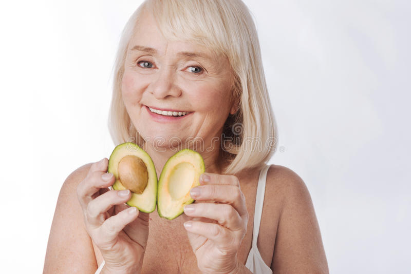 Nice delighted woman putting two avocado halves together stock photography