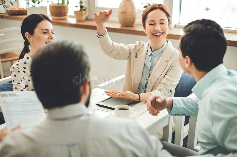 Nice delighted woman talking to her colleagues. Interaction between colleagues. Nice delighted women sitting at the table while talking to her colleagues royalty free stock photo