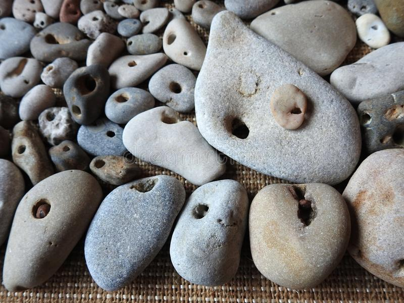 Nice different colors and shape stones with hole, Lithuania stock images