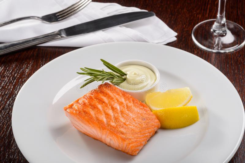 Nice dinner for a gourmet. With a cutlery and a glass of wine. Tasty salmon steak with Wasabi sauce and segments of a lemon stock image