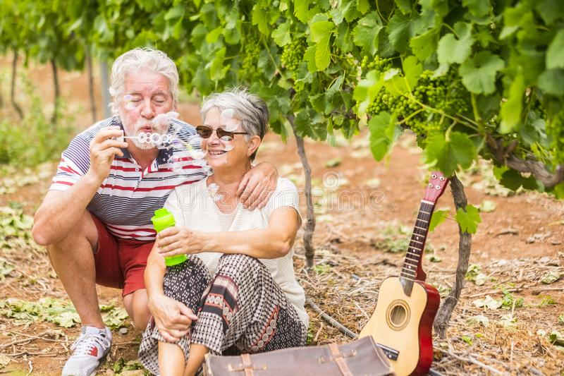 Nice elderly people senior adult play together outdoor in the nature with bubble soap like young guys. together forever in love royalty free stock photography