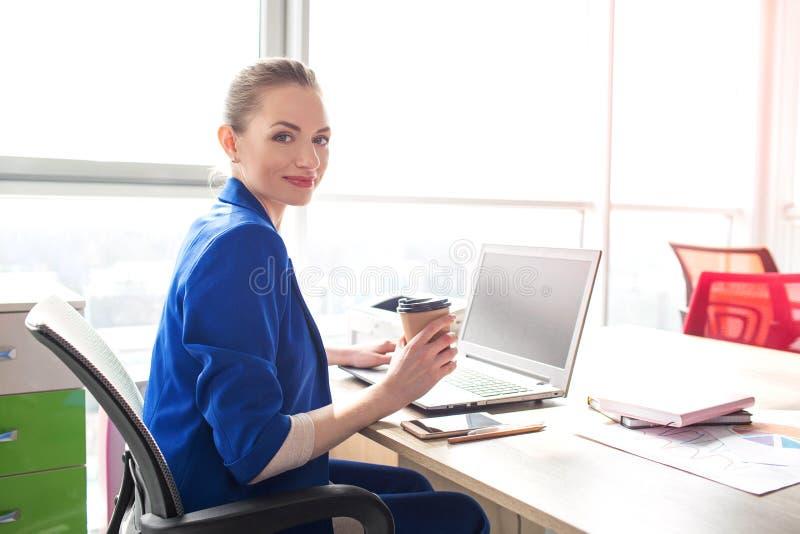 Nice en de mooie bedrijfsvrouw zitten bij de lijst in bureau en kijken aan de camera Zij houdt een kop van stock foto
