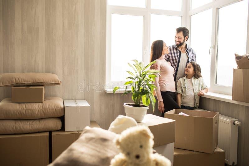 Nice en heldere flat De jonge en gelukkige familie heeft zich enkel het bewegen in het Er zijn dozen overal met hun materiaal stock afbeelding
