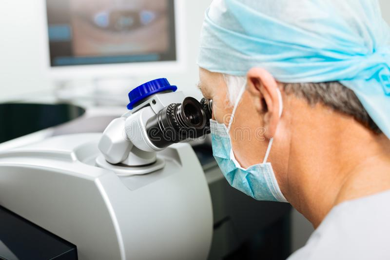 Nice experienced doctor doing the vision diagnostics royalty free stock photos