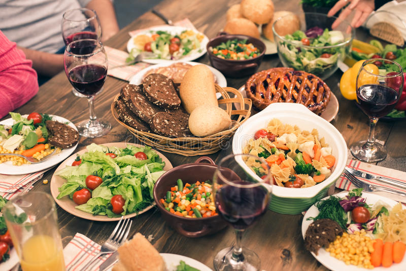 Nice family having tasty dinner. Family dinner. Tasty food on table. There are organic fresh meal: bread, pie, pasta, vegetable salad royalty free stock images