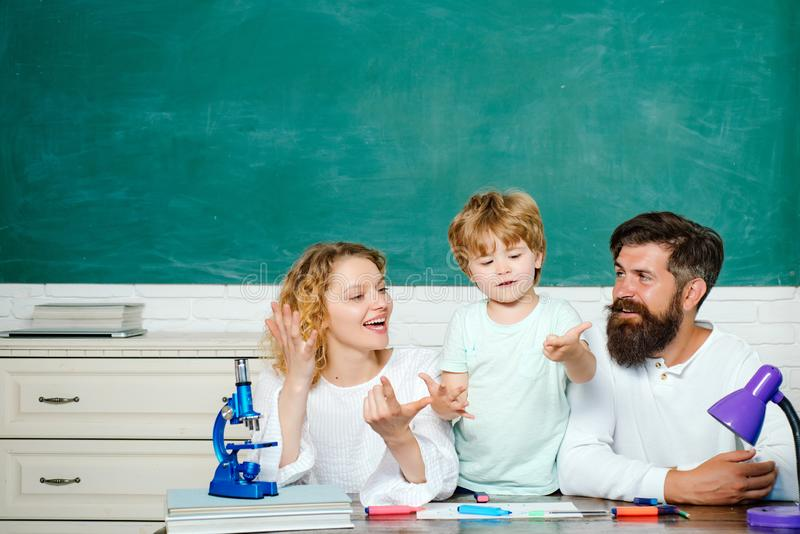 Nice family photo of little boy and his Parents. Young happy family schooling math together. Woman and man helps the. Child boy. Family school partnership. Back stock photography