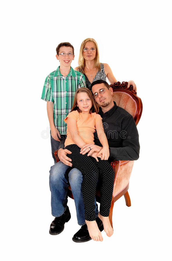 Nice family picture. A young family, mom, dad, daughter and son, isolated for white background sitting in a pink armchair royalty free stock photos