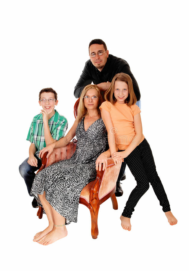 A nice family portrait. A family group, the mom sitting in a pink armchair and the husband, daughter and son standing, isolate for white background royalty free stock images
