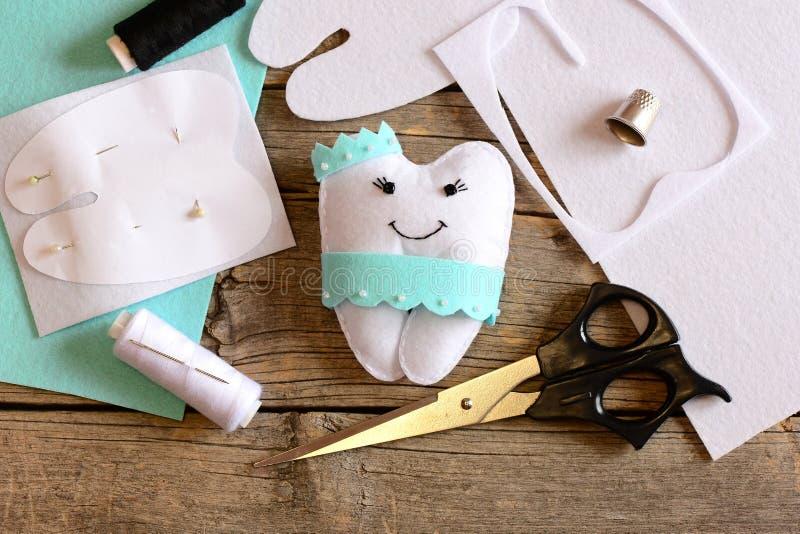 Nice felt tooth fairy pillow, paper template, felt sheets and scraps, scissors, thread on vintage wooden background. Felt crafts. Simple felt crafts. Needlework stock image