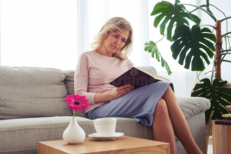 Nice female of age 40-50 concentrating on reading book royalty free stock photo