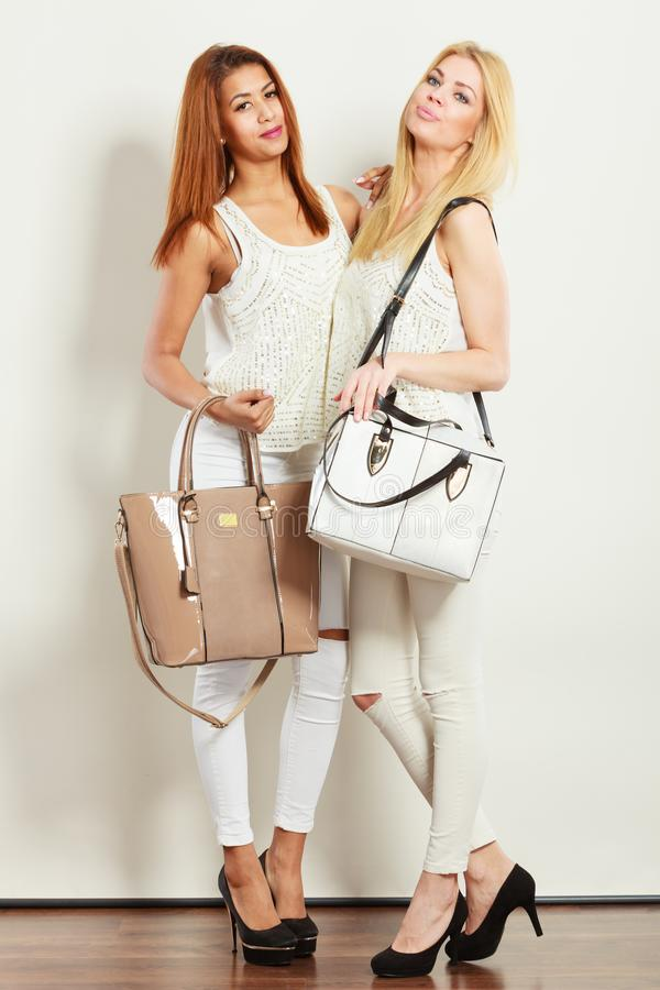 Nice female friends with handbags stock photography