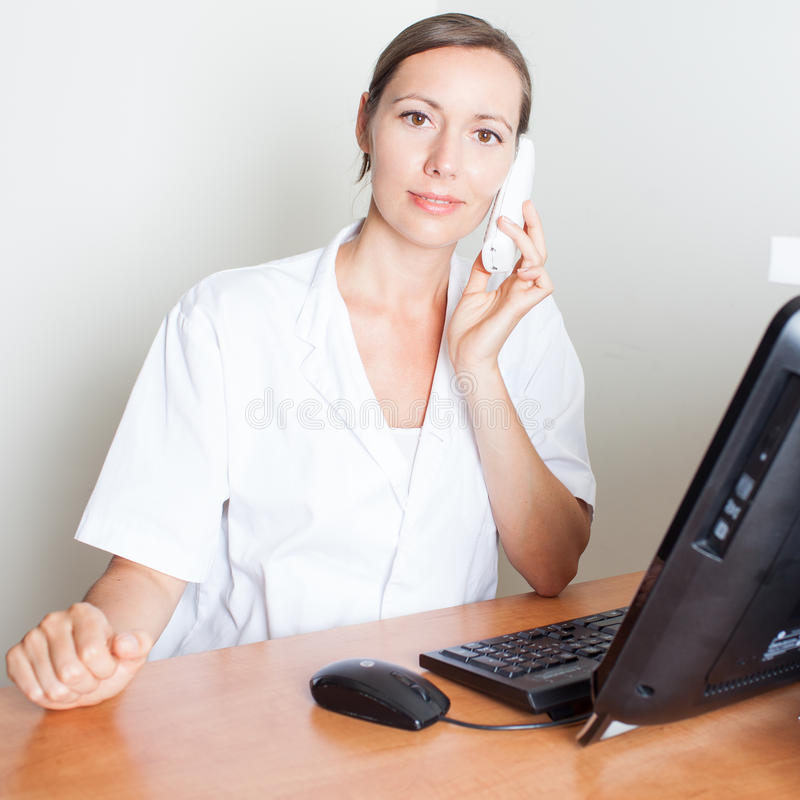 Nice female medical receptionist smiling. Medical receptionist on phone in front of computer stock images