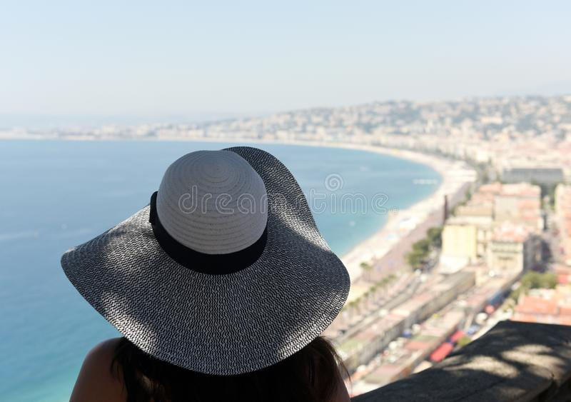 Woman in a hat looks at the beach and promenade of Nice royalty free stock photography