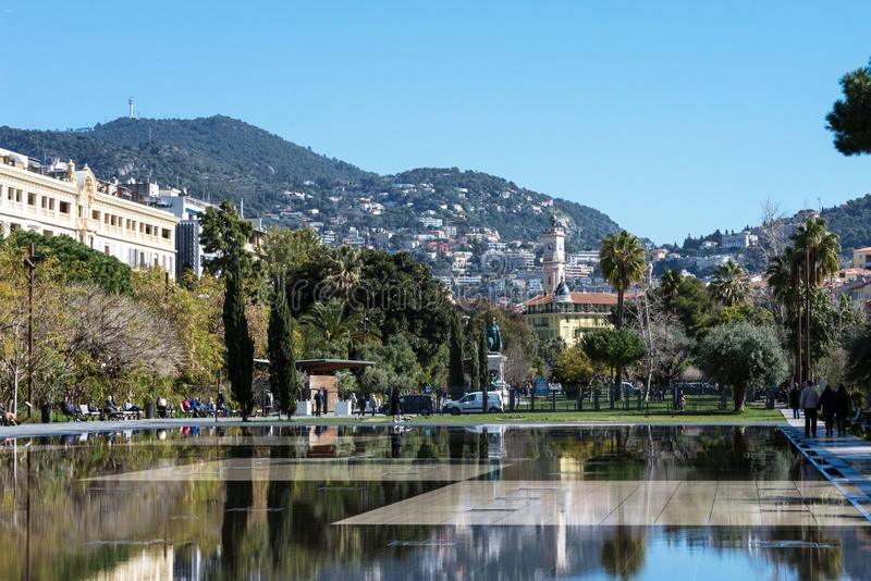 Nice, France, March 2019. Fountain on the embankment du Pillon on a warm sunny day. Reflection of the city in the water. Walk on. The Cote d`Azur royalty free stock photo