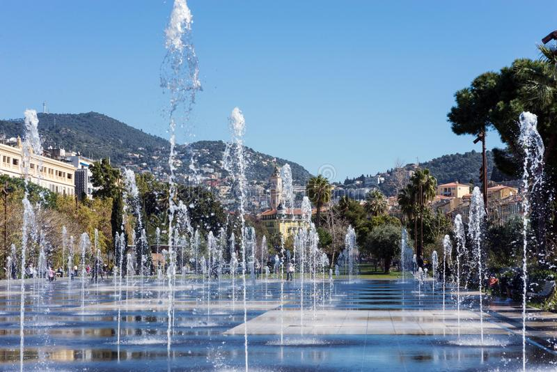 Nice, France, March 2019. Fountain on the embankment du Pillon on a warm sunny day. Reflection of the city in the water. Walk on stock images