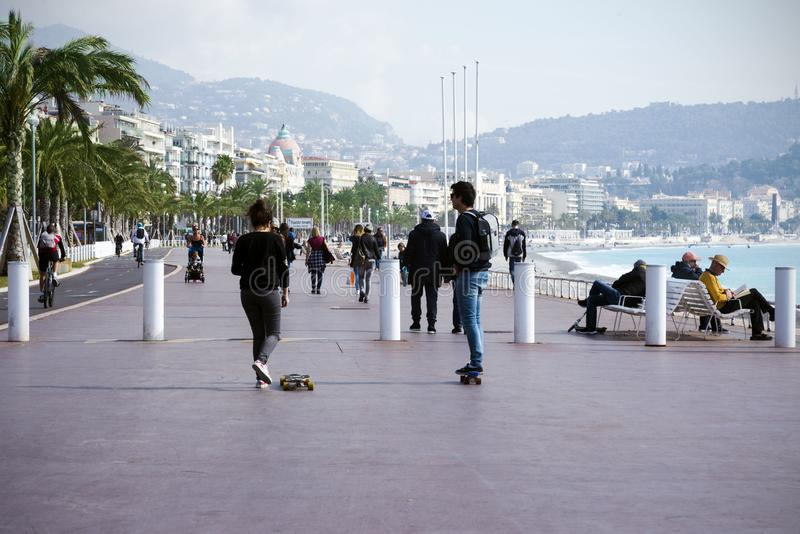 Nice, France, March 2019. Two young people: a boy and a girl ride a skateboard along the promenade. Cote d`Azur. royalty free stock photos