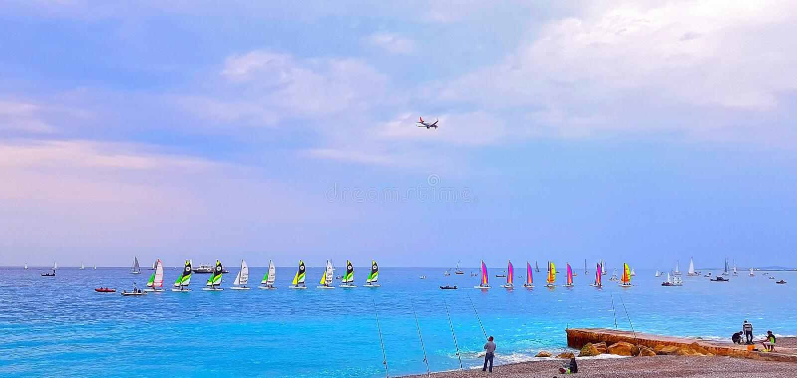 NICE, FRANCE - MAY 2018: Beach at sunset, colorful sailboats in the sea, airplane flying over the sea, Cote d`Azur, France. NICE, FRANCE - MAY 2018: Beach at stock image