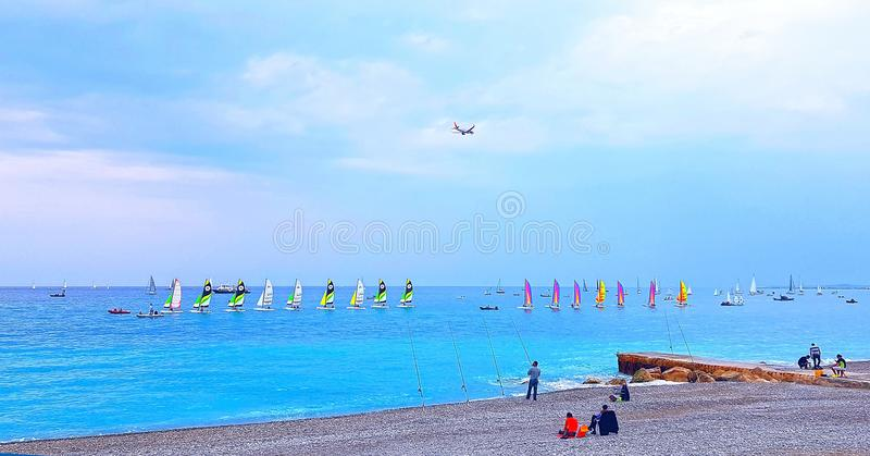 NICE, FRANCE - MAY 2018: Beach at sunset, colorful sailboats in the sea, airplane flying over the sea, Cote d`Azur, France. NICE, FRANCE - MAY 2018: Beach at stock photos