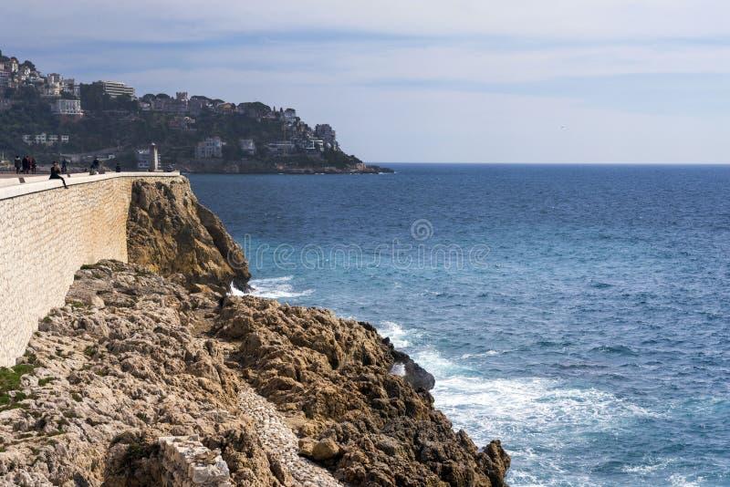 Nice, Frankrijk, Maart 2019 Mooie turkooise overzees, bergen in de nevel en de dijk van Promenade des Anglais op warm stock foto's