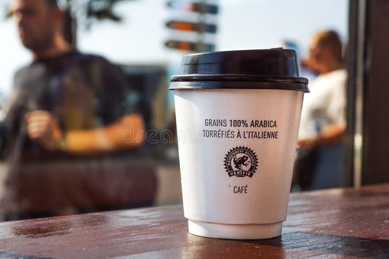 Nice Frankrike -02 august 2017: Pappers- kaffekopp från coffee shop på träbakgrund royaltyfri foto