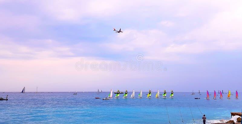 NICE FRANKRIKE - MAJ 2018: Sätta på land på solnedgången, färgrika segelbåtar i havet, flygplanet som flyger över havet, ` Azur,  royaltyfria bilder