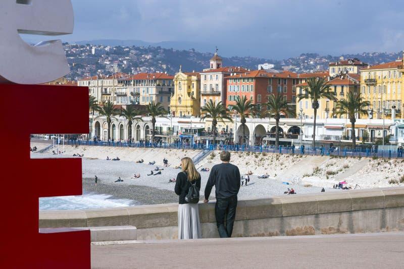 Nice Frankrike, mars 2019 panorama Azurt hav, vågor, engelsk promenad och vila för folk Unga par: en man och en kvinnablick royaltyfria foton