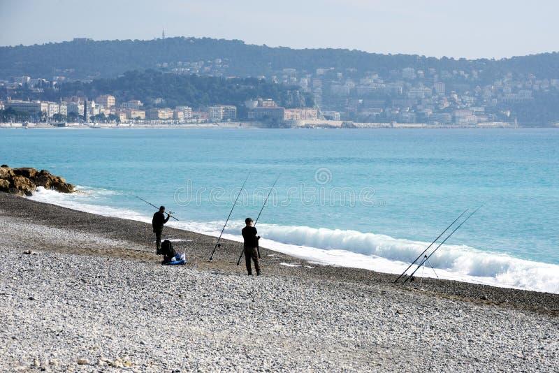 Nice Frankrike, mars 2019 Två fiskare som fiskar med metspön på Pebblet Beach av Nice ` Azur för skjul D Ljusa dimmahängningar öv arkivfoton