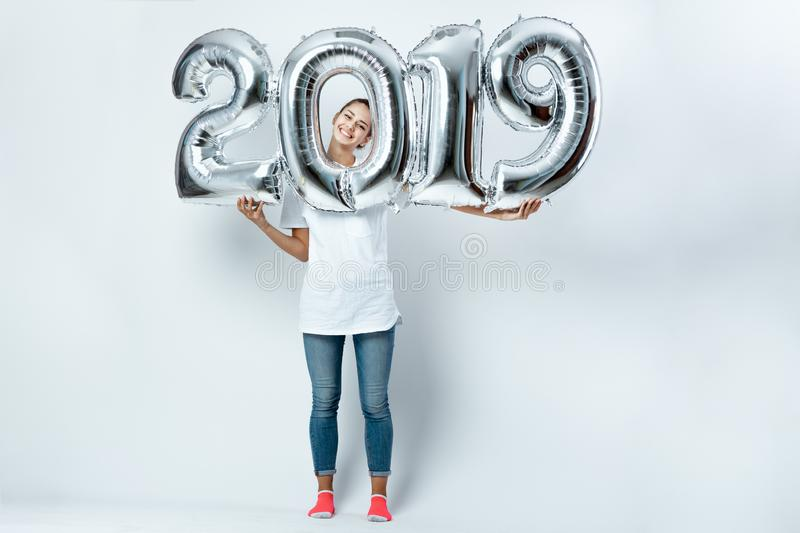 Nice funny girl dressed in white t-shirt, jeans and pink socks holding balloons in the shape of numbers 2019 on the royalty free stock photo