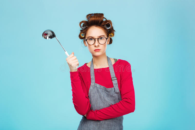 Nice funny girl hides from dangerous ladle and standing on blue background. royalty free stock photo