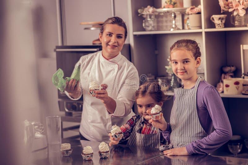 Nice geconcentreerd meisje die cupcake bekijken royalty-vrije stock afbeeldingen
