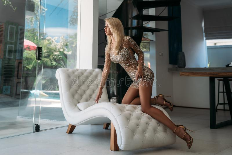 A nice girl with a beautiful figure in a short shiny dress rests on a white stylish sofa in the studio. Portrait of an. Elegant girl with long legs in an stock photo