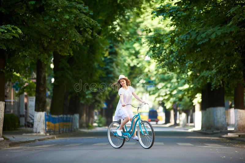 Nice girl on bike alone at road. Summer sunny day. royalty free stock image