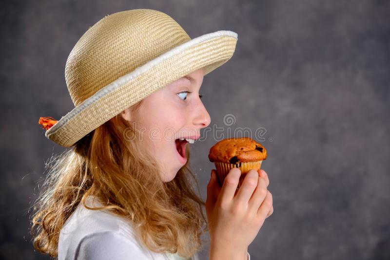 Blond girl in white dress and straw hat eating muffin stock photography