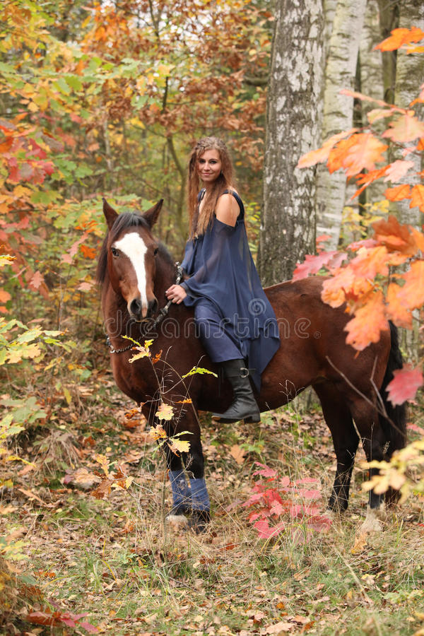 Nice girl with brown horse in autumn stock photos