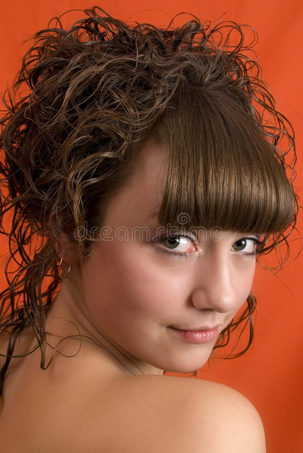 Nice girl with curly hair. Over red background stock image