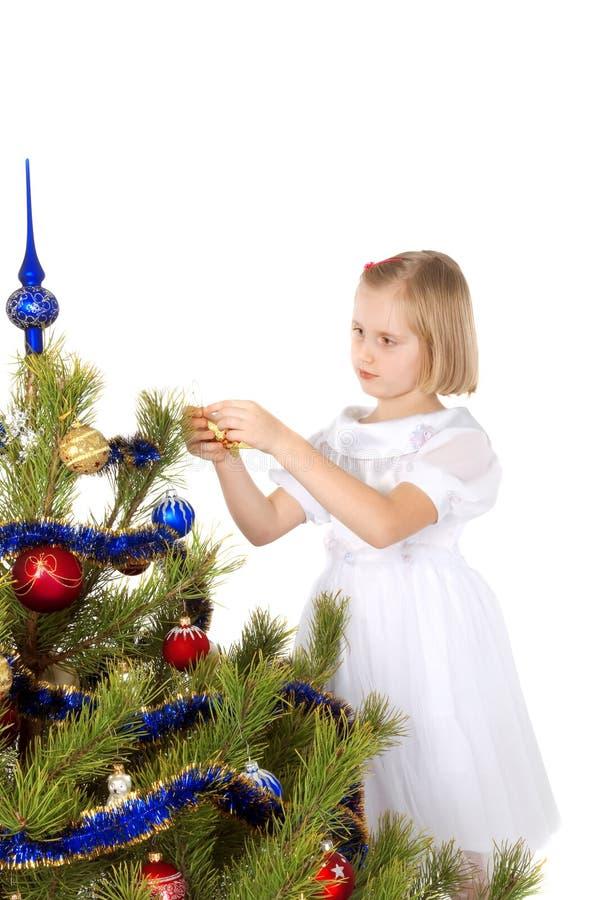 Nice girl decorates a Christmas tree stock image