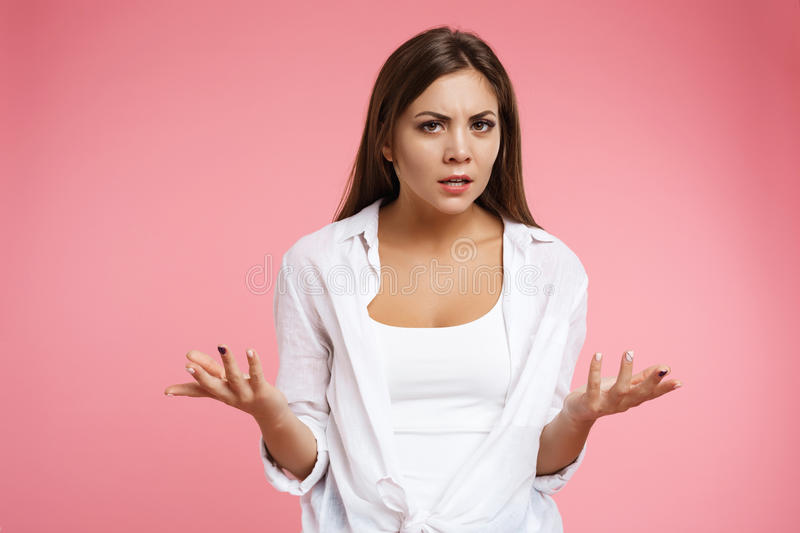 Nice girl doesn t understand what` s going on waving hands royalty free stock image